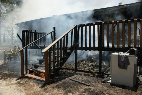A cooker on the back deck likely caused a fire that seriously damaged a house in the 3900 block of Union Church Road in Vass house and killed some pets Saturday, July 4, 2009. (Photo courtesy of Frank Staples, Circle V Fire Department)