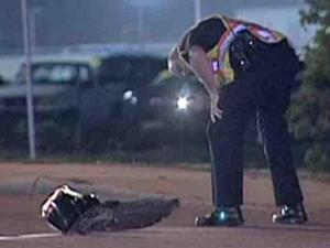 A Fayetteville police officer examines a piece of wreckage after a vehicle struck and killed a man on Sycamore Dairy Road, near Bragg Boulevard, early Saturday, July 25, 2009, Fayetteville police said.