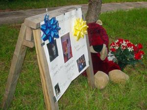A teddy bear and bouquet of roses lie next to a sign with pictures of Shamika Nikkia Lett, 17, who shot to death on Hickory Avenue, at Fourth Street, Wednesday, Aug. 5, 2009. Residents held a candelight vigil a day later. (Viewer-submitted photo)
