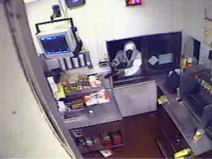 Surveillance video shows a black man wearing a white hooded sweatshirt reaching into the drive-through window.