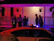 Holly Springs police officers stand outside a home at 703 S. Main St. An officer sustained minor injuries while breaking up a fight at the house. A man had been stabbed at the house shortly before midnight Friday. (Photo by Thomas Babb)