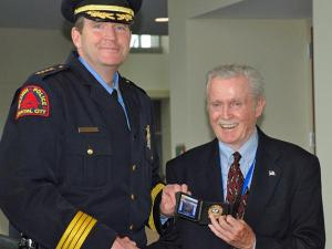 Raleigh Police Chief Harry Dolan presents Frederick K. Heineman with a badge for retired police officers in 2008.