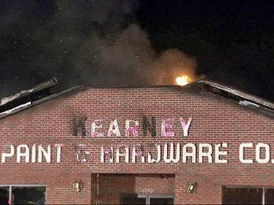 Flames rip through the roof at Kearney Paint and Hardware Company.