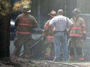 Firefighters investigate a house fire on Saturday, July 24, 2010, at 7011 Farmdale Road, in Raleigh.