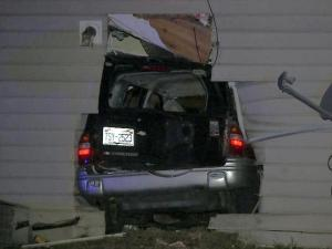 An SUV carrying at least three people, including one shooting victim, crashed into a house on the way to a local hospital Monday night, June 13, 2011.