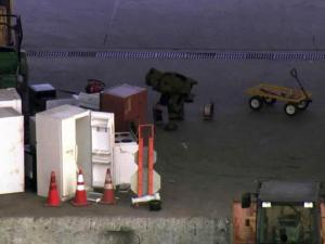 A member of the Durham County Sheriff's Office bomb squad checks a refrigerator dropped at a landfill on East Club Boulevard for possible explosives on Dec. 29, 2011.