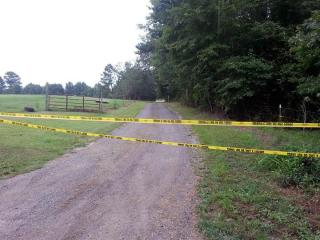 Crime scene tape blocks a gravel drive at 1569 Crantock Road in Smithfield, where a man was found dead in a creek on Aug. 29, 2012, after a mowing accident.