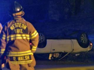 Firefighters stand near a Mazda Miata that hit a power pole and overturned on Wade Avenue, near Faircloth Street, injuring the driver on Dec. 23, 2012.