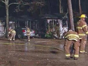 Firefighters clean up after extinguishing a blaze that gutted a mobile home in Knightdale on Nov. 26, 2013.