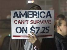 A protester holds a sign outside a Burger King on Capital Boulevard on Thursday, Dec. 5, 2013.