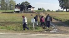 Family members walk outside the house where an elderly couple died in a fire April 22, 2014.