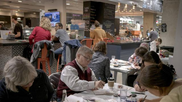 """Volunteers write postcards to voters at a """"Postcards for Voters"""" event at Soapstone Market in Washington, Oct. 29, 2018. A grass roots army of almost 40,000 is hand writing postcards to voters on behalf of Democratic candidates. Whether it works is open to debate. (Gabriella Demczuk/The New York Times)"""