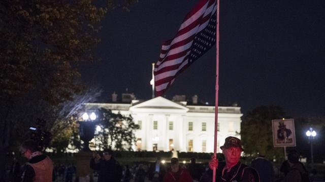 "Michael Marceau holds and upside down American flag at a ""Protect Mueller"" protest at Lafayette Square in Washington, Nov. 8, 2018. President Donald Trump fired Attorney General Jeff Sessions the day after the midterms, a move that raised immediate questions about how the special counsel's Russia inquiry would be affected. (Sarah Silbiger/The New York Times)"