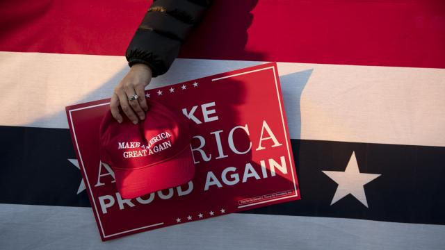 An attendee's cap and sign at President Donald Trump's campaign event on behalf of Sen. Cindy Hyde-Smith in Tupelo, Miss., Nov. 26, 2018. Some two million federal employees have been told that making or displaying statements at work about impeaching or resisting Trump is likely to amount to illegal political activity. (Sarah Silbiger/The New York Times)