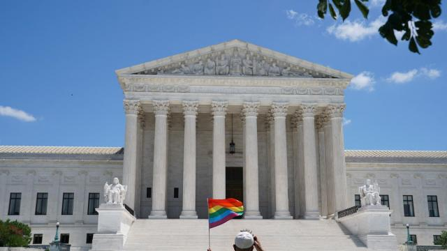 A person waves a rainbow flag in front of the Supreme Court in Washington, on Monday, June 15, 2020. The Supreme Court ruled Monday that a landmark civil rights law protects gay and transgender workers from workplace discrimination, handing the movement for L.G.B.T. equality a stunning victory. (Anna Moneymaker/The New York Times)