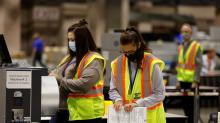 IMAGE: Workers whittle down piles of uncounted ballots in key states