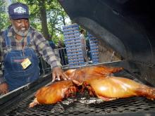 Pitmaster Ed Mitchell of Wilson, N.C., checks one of the whole hogs he cooked at the Second Annual Big Apple Barbecue Block Party, in New York City, Saturday, June 12, 2004. (AP Photo/Richard Drew)