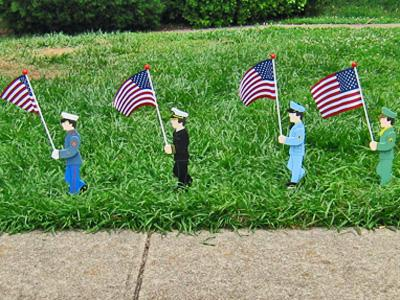 A line of wooden figures represent the U.S. Armed Forces in the lawn of a Smallwood Drive home in Raleigh on Saturday, May 24, 2008. (Photo by Inga Brown)