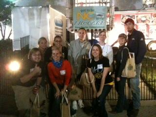 Team WRAL poses with another team in front of the giant grocery cart at the fair.