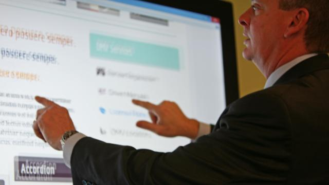 State Chief Information Officer Chris Estes demonstrates prototypes of new government agency websites in the Innovation Center on Jones Street Dec. 13, 2013.