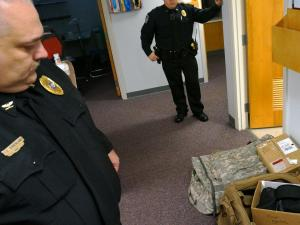 Bethel Police Chief Troy Strickland walks past a pile of military surplus equipment his agency received from the 1033 excess property program Dec. 9, 2014. The equipment includes gear bags and safety glasses officers use for firearm training. (Tyler Dukes/WRAL)