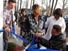 Bobby and Regina McDonald cut the ribbon at dedication of their new home in La Grange