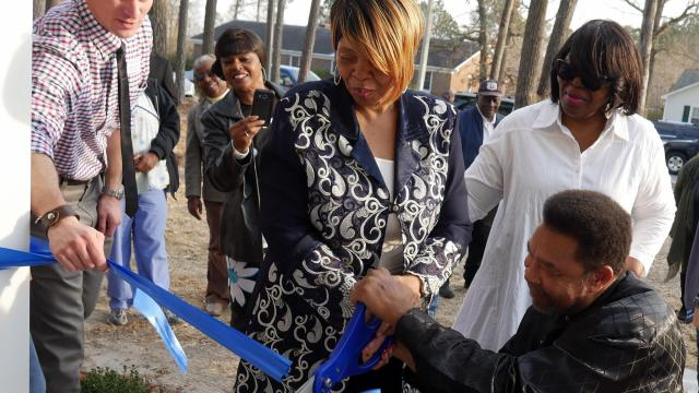 Matthew Whittle, the Goldsboro-Wayne County Habitat for Humanity affiliate executive director, catches the ribbon as Bobby and Regina McDonald make the cut at the dedication of their new home in La Grange.