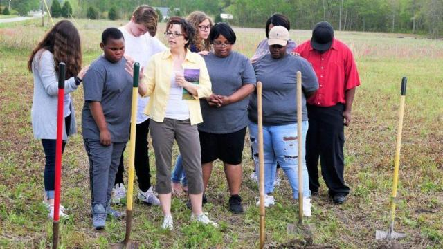 Pastor Marcie Friesner of TJ's Church, in yellow jacket, leads a prayer at the groundbreaking at the Habitat for Humanity SECU Challenge home site in Onslow County. Joy Mattocks, the new homeowner, is at Friesner's left. They are flanked by Mattocks' children Rueben, 12, at Friesner's right, and Dequisha, 21, at her mother's left.