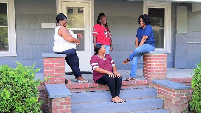 Homeowner Jannie Swain, left, enjoys some quality time on her new porch with her sisters Vaniqua Brown, on steps; Bobby Douglas, standing; and Diana Swain, right.