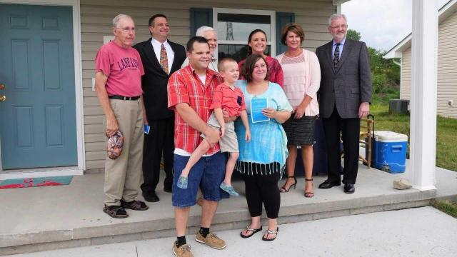David Parnell and Stephanie Jones with their son at the dedication of their new home in Henderson County.