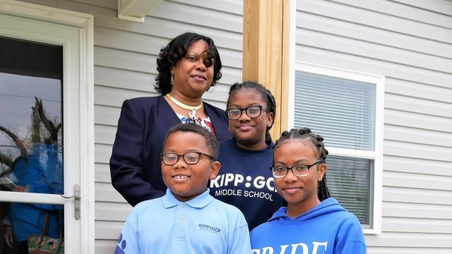 The family is ready to move in: Shamera Williams with three of her children, from top: Jessica, a fifth-grader; Jayson, a third-grader, and Destiny, a high school sophomore. Williams' oldest child, Aviana, is a sophomore at the University of Southern California and did not make it home for the dedication. The house was built as part of the State Employees Credit Union Foundation's Mountains-to-the-Sea Challenge, to build a Habitat for Humanity home in each of North Carolina's 100 counties.