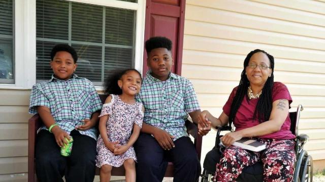 Portia Smith on the porch of her new home with her children, from left, DeKetren, A'Niya and Ja'Quis.