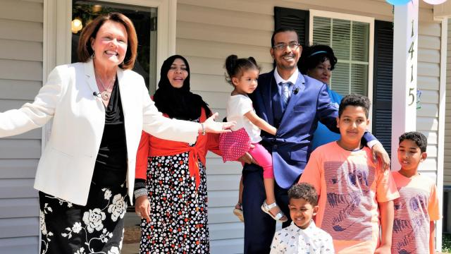 Maria Hanlin, left, president and CEO of Habitat for Humanity of Greater Greensboro, welcomes the crowd at the dedication of the home of Abdelrhman Elbahi and Abir Mohammed and their four children.