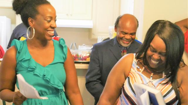 Tiffany Brown, left, Homeowner Services coordinator for Habitat for Humanity of Cabarrus County, shares the joy of the moment with new homeowner Paditra Carlton. Behind Paditra is her father, the Pastor Ervin Carlton, who gave the house blessing.