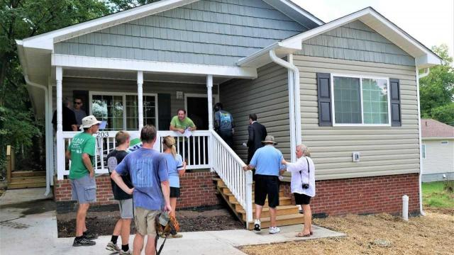 Habitat for Humanity volunteers walk into Charlotte Furaha's new home in High Point during the dedication ceremony. The home is in the Washington Terrace neighborhood, which Habitat for Humanity of High Point, Archdale and Trinity is developing.