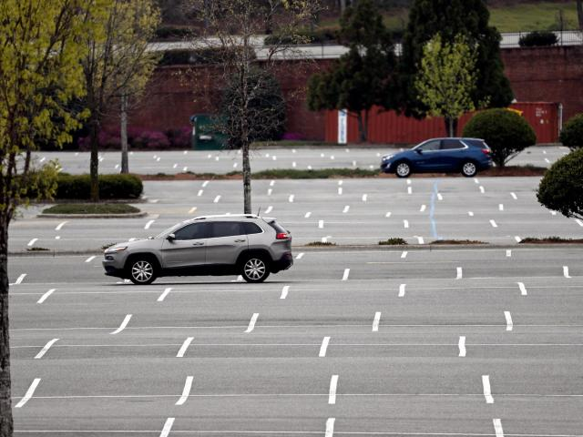 Cars drive through an empty parking lot at Southpoint Mall in Durham, N.C., Tuesday, March 24, 2020. Many non-essential businesses have closed during the coronavirus outbreak as shoppers stay away. (AP Photo/Gerry Broome)