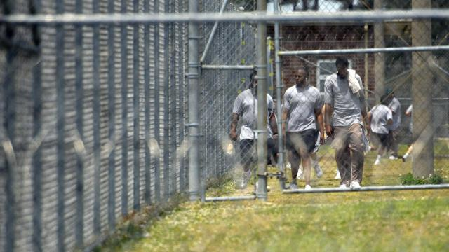 Inmates at Neuse Correctional Institution walk outside behind fences in Goldsboro on May 15, 2020. As of that date, the prison had reported three inmate deaths and 467 positive tests out of 702 inmates tested (Melissa Sue Gerrits / Carolina Public Press).