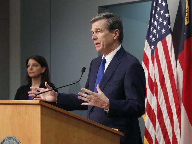 North Carolina Gov. Roy Cooper answers a question during a briefing on the coronavirus pandemic at the Joint Force Headquarters in Raleigh on May 20, 2020, as N.C. Department of Health and Human Services Secretary Mandy Cohen looks on (Photo courtesy N.C. Department of Public Safety