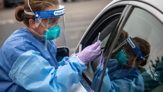 Kelly Mendenhall performs a coronavirus test at a drive-through testing site in Burlington Thursday, July 16, 2020, as healthcare workers work through July heat to test hundreds of people per day (Travis Long/The News & Observer).