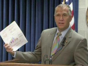 House Speaker Thom Tillis displays the 2011-12 state budget that lawmakers passed over Gov. Beverly Perdue's veto during a June 16, 2011, news conference.
