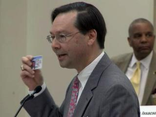 Hans von Spakovsky of the Heritage Foundation holds up his driver's license during a March 13, 2013, House Elections Committee hearing on a voter ID proposal.