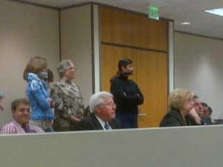 Three adults were standing to protest the progress of a charter school bill in Senate Education Committee on 4/3/2013.