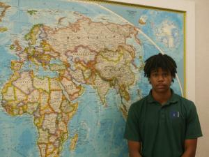 Aspen Harris, a senior at Southern Wake Academy, wears a uniform shirt in front of a world map in the school's hallway.