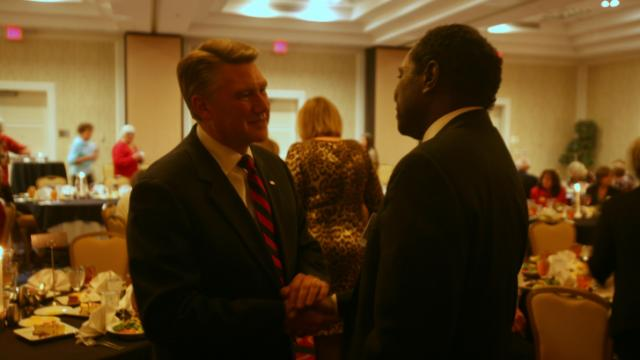 Mark Harris, a Baptist preacher and candidate for U.S. Senate, shakes hands with Alan Foster, of Raleigh, before an event hosted by the N.C. Federation of Republican Women on Nov. 8, 2013.