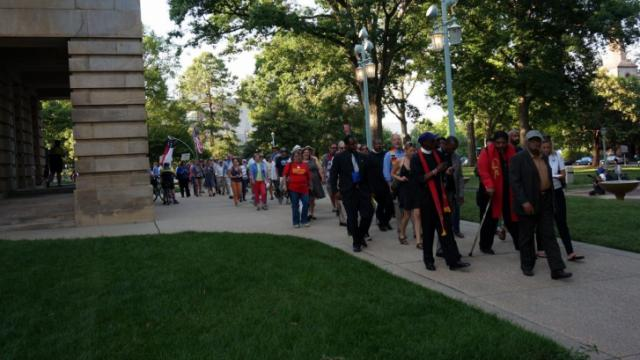 """Lea by the Rev. William Barber, protesters with the """"Moral Monday"""" movement walk around the state Capitol building on June 2, 2014, after being unable to deliver a petition to state Senate leaders at the Legislative Building."""