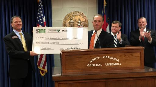 NC food banks director Alan Briggs (L) accepts a $50,000 check from NC Retail Merchants Association director Andy Ellen.
