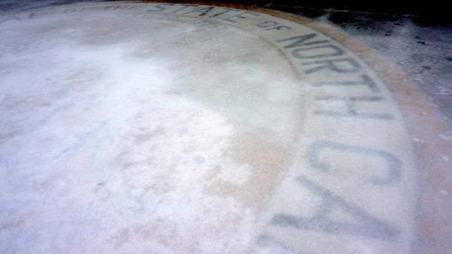 The Great Seal of North Carolina in front of the legislative building covered by ice.