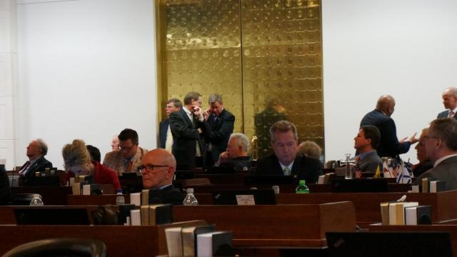 Reps. Charles Jeter, R-Mecklenburg, and Paul Tine, U-Dare, confer in the back of the House chamber on April 29, 2015, as fellow lawmakers debate legislation.