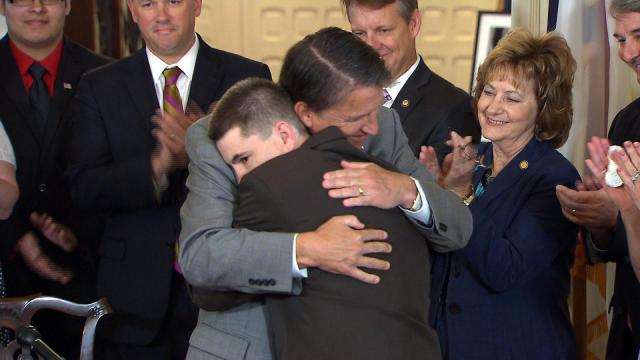 Gov. Pat McCrory hugs nursing home abuse victim Burt Powell during a May 26, 2015, ceremony in which McCrory signed Burt's Law legislation making it a crime to abuse group home patients or fail to report such abuse.