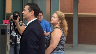 Dana Cope, former director of the State Employees Association of North Carolina, is flanked by his wife, Melinda Cope, and attorney, Roger Smith, as he turns himself in Tuesday. Cope, who is charged wtih two counts of obtaining property by false pretense, is accused of spending the organization's money on personal items.